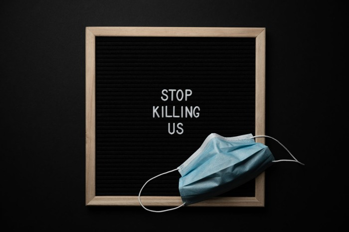 """Photo of a disposable blue mask in front of a wooden sign with the words """"Stop Killing Us"""""""