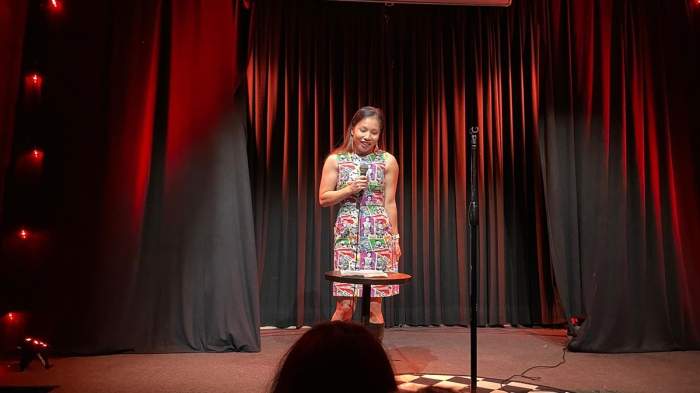 Photo of Vivian Chandra standing on a stage in front of a red curtain wearing a colourful Star Wars dress