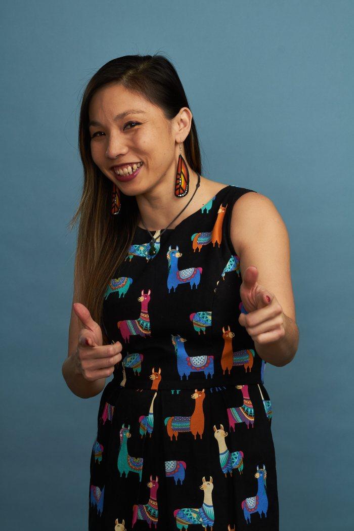 Photo of Vivian Chandra in a llama dress doing pistol fingers
